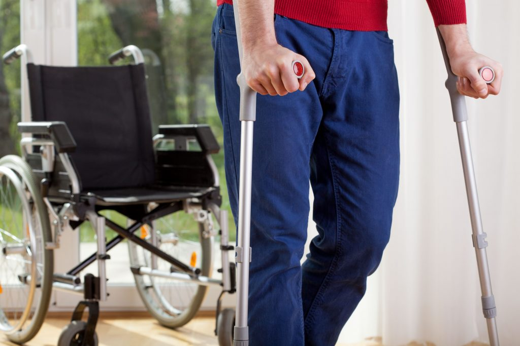 Disabled man walks with crutches. These is a wheelchair in the background