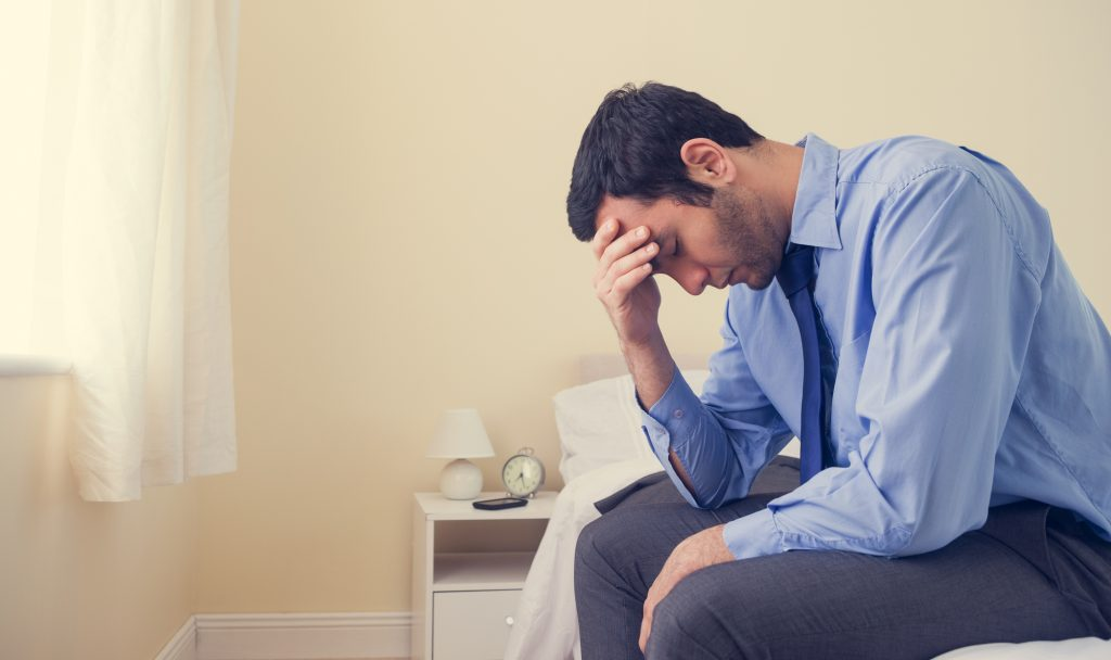 man distressed sitting on a bed with hand on his head